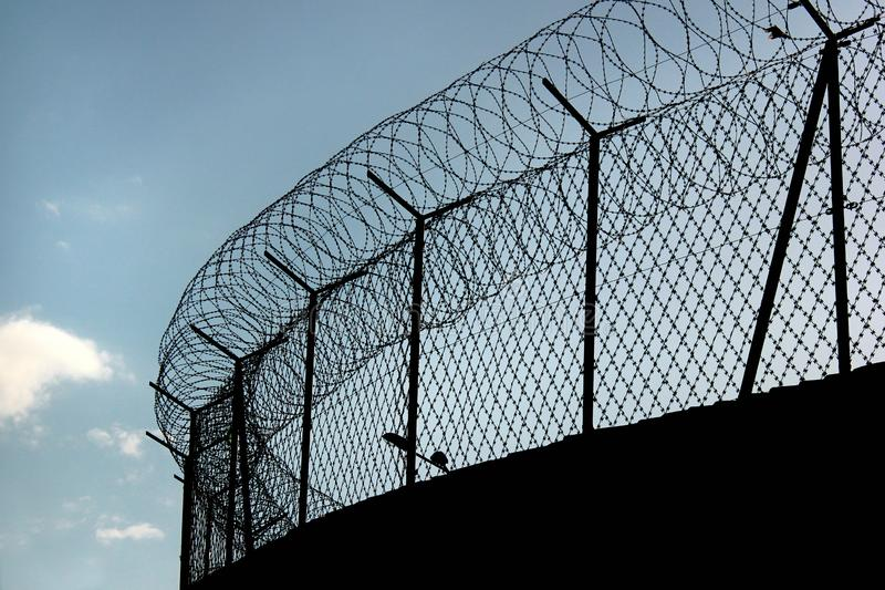 Silueta del alambre de púas acordeón en una cerca de la prisión fotos de archivo libres de regalías
