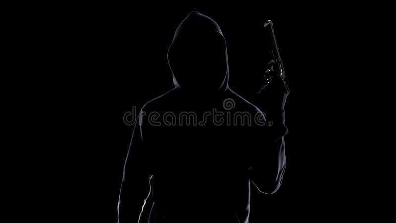 Silueta del asesino en serie en la sudadera con capucha que amenaza con el arma, preparándose para asesinar imagen de archivo