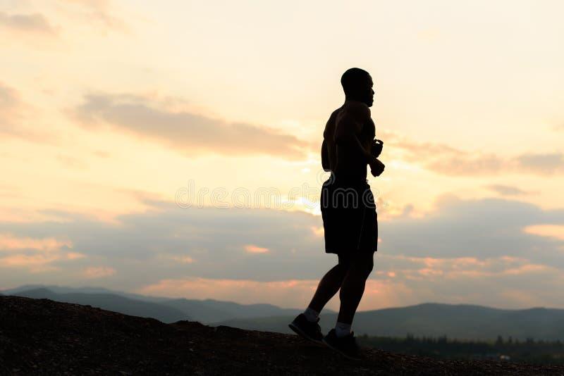 Silueta del atleta afroamericano que activa en puesta del sol en montañas imagenes de archivo
