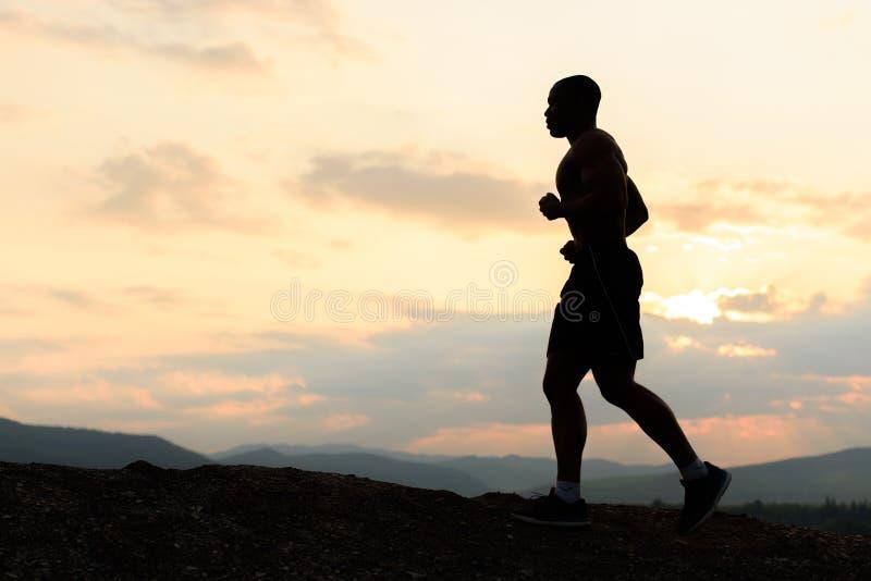 Silueta del atleta afroamericano que activa en puesta del sol en montañas Entrenamiento al aire libre foto de archivo