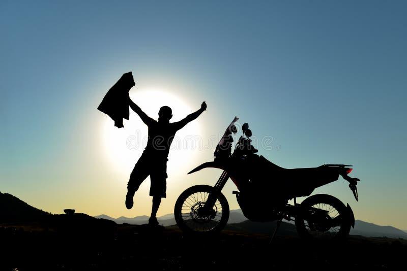 Silueta del aventurero de la motocicleta y feliz foto de archivo