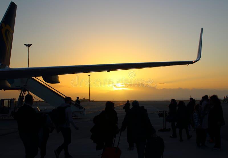 Silueta del avión de pasajeros en la puesta del sol foto de archivo