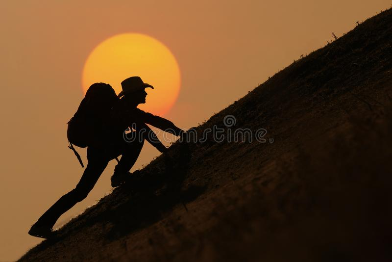 Silueta del backpacker que sube en la montaña imagen de archivo