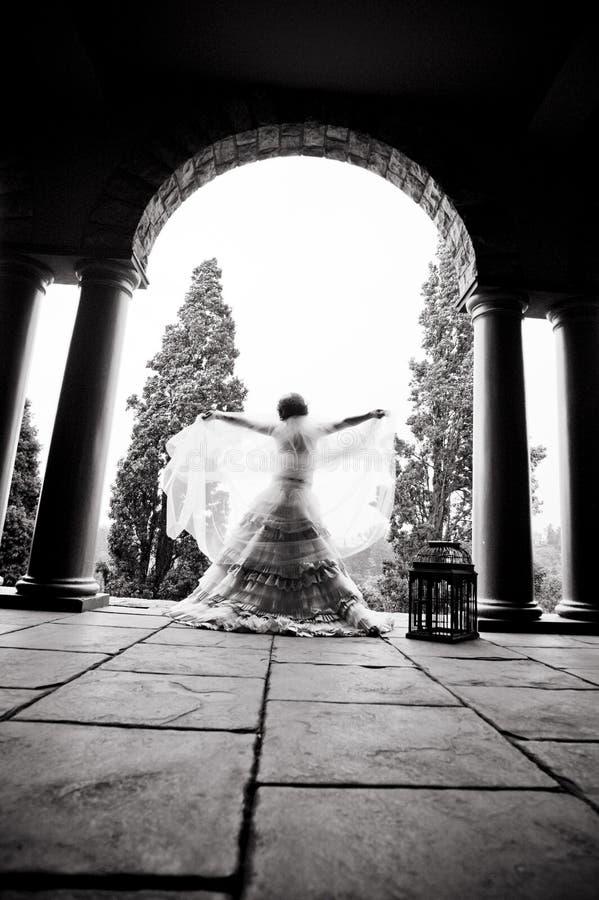 Silueta del baile hermoso joven de la novia debajo de un tejado sostenido con pilares foto de archivo libre de regalías