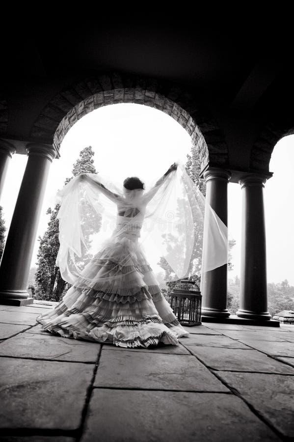 Silueta del baile hermoso joven de la novia debajo de un tejado sostenido con pilares fotos de archivo