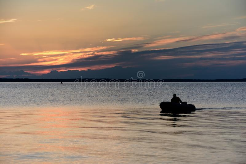 Silueta del barco con el pescador contra la perspectiva de una disminución hermosa en el banco del lago imagen de archivo libre de regalías