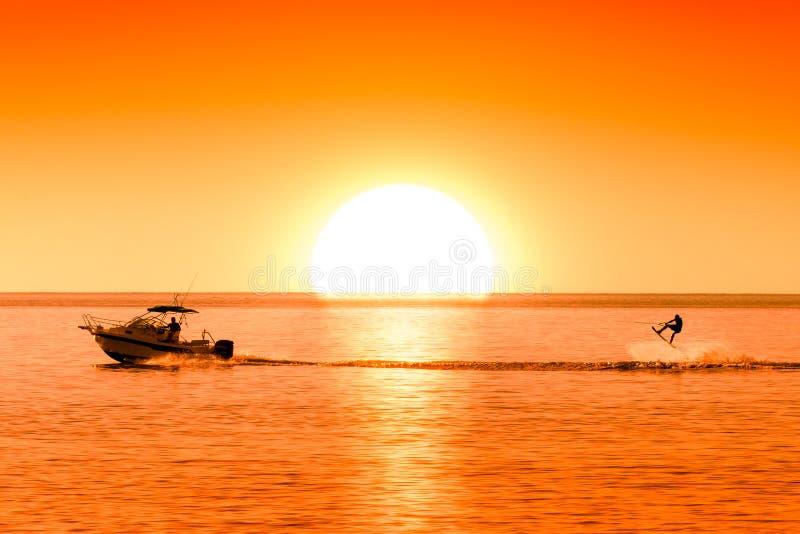 Silueta del barco de motor y del wakeboarder en la puesta del sol que realiza truco imagenes de archivo