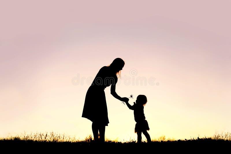 Silueta del bebé que da la flor de la mamá en la puesta del sol foto de archivo