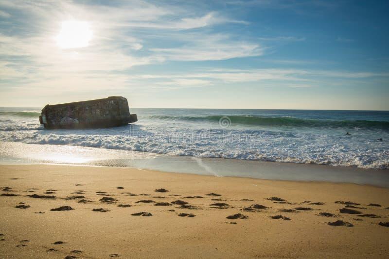 Silueta del blocao de la guerra en paisaje marino hermoso escénico de la playa arenosa con las ondas en Océano Atlántico foto de archivo