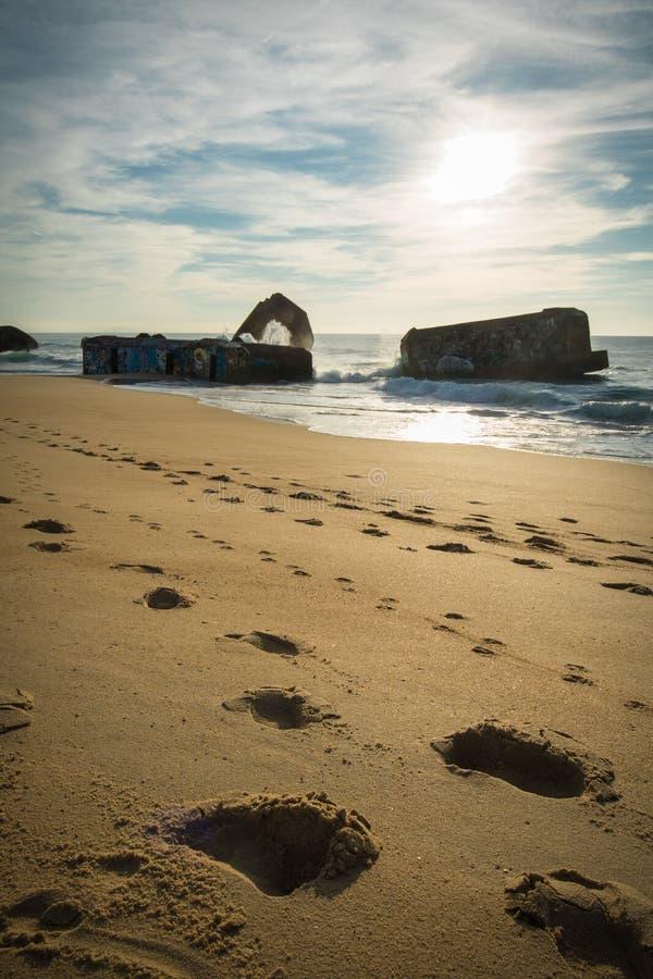 Silueta del blocao de la guerra en paisaje marino hermoso escénico de la playa arenosa con las ondas en Océano Atlántico imagenes de archivo