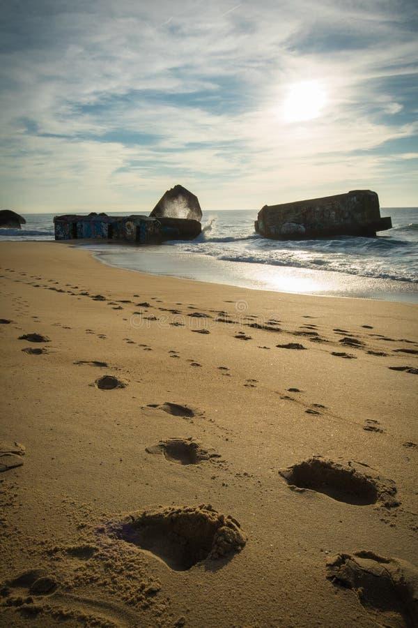 Silueta del blocao de la guerra en paisaje marino hermoso escénico de la playa arenosa con las ondas en Océano Atlántico fotografía de archivo