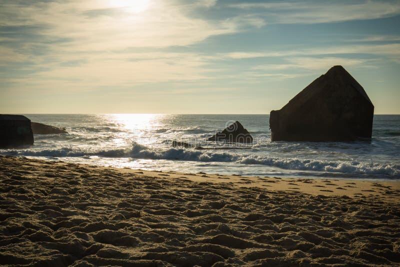 Silueta del blocao de la guerra en paisaje marino hermoso escénico de la playa arenosa con las ondas en Océano Atlántico en cielo imagenes de archivo
