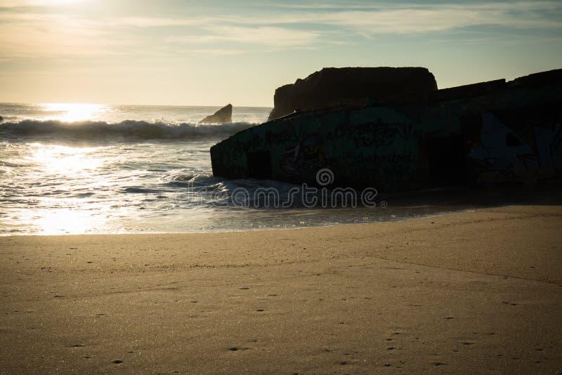 Silueta del blocao de la guerra en paisaje marino hermoso escénico de la playa arenosa con las ondas en Océano Atlántico en cielo imagen de archivo