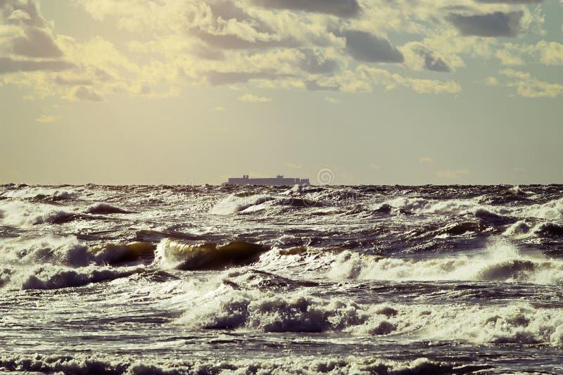 Silueta del buque de carga en el horizonte Navegación grande del portacontenedores a través de las ondas tempestuosas del mar Bál imagen de archivo