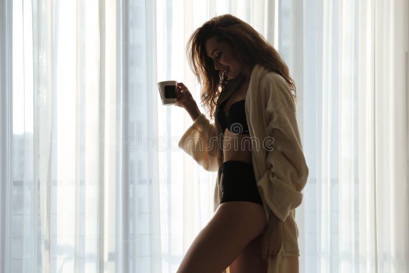 Silueta del café de consumición sensual de la mujer joven cerca de la ventana imagen de archivo