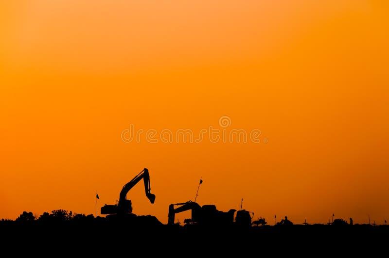 Silueta del cargador de excavador en el emplazamiento de la obra, retroexcavadora de la silueta fotografía de archivo libre de regalías