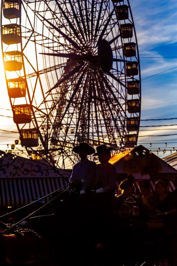 Silueta del carro y de la noria del caballo en la puesta del sol ` S April Fair de Sevilla foto de archivo libre de regalías