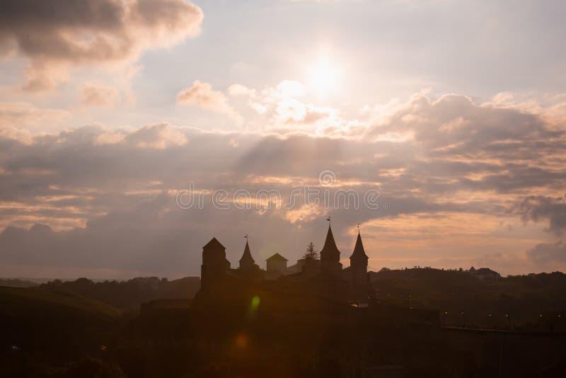 Silueta del castillo medieval Kamianets-Podilskyi del fortalecimiento en puesta del sol foto de archivo