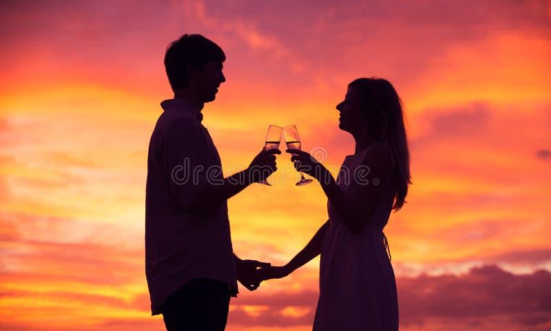 Silueta del champán de consumición de los pares en la puesta del sol imágenes de archivo libres de regalías