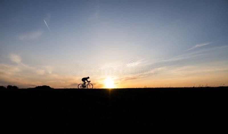 Silueta del ciclista en el movimiento en el fondo de la puesta del sol hermosa Bicicleta masculina del paseo en sistema del sol S foto de archivo