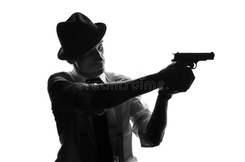 Silueta del detective con dos armas imágenes de archivo libres de regalías