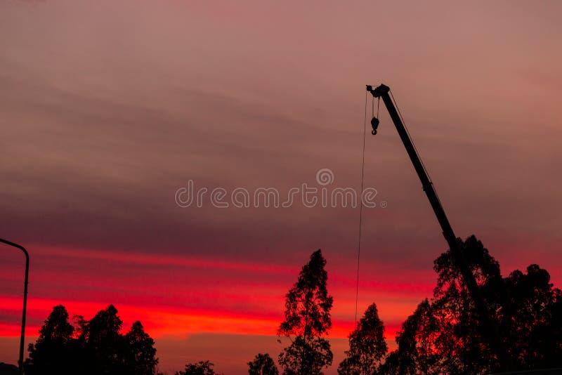 Silueta del emplazamiento de la obra en fondo de la puesta del sol foto de archivo