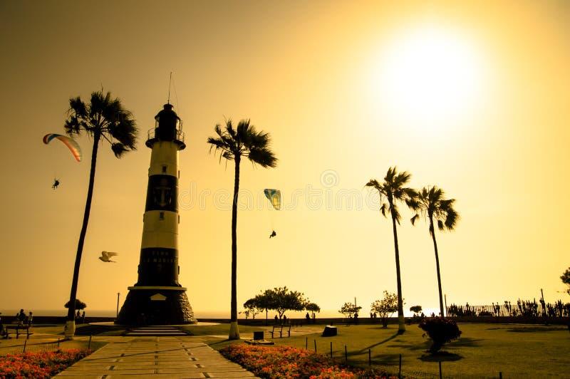 Silueta del faro entre el mar de oro de la puesta del sol fotografía de archivo libre de regalías
