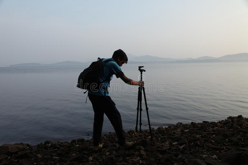 Silueta del fotógrafo con el trípode Hombre joven que toma la foto con su cámara por la mañana cerca del lago en la India imagenes de archivo
