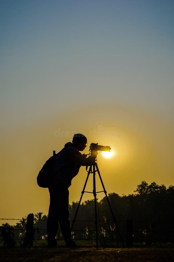 Silueta del fotógrafo contra el sol imagenes de archivo