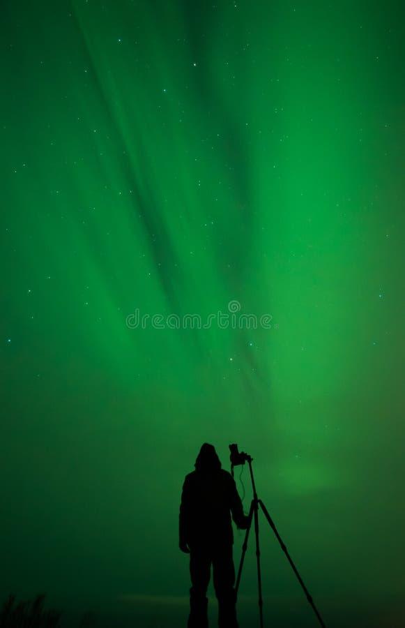 Silueta del fotógrafo de la aurora boreal imagenes de archivo