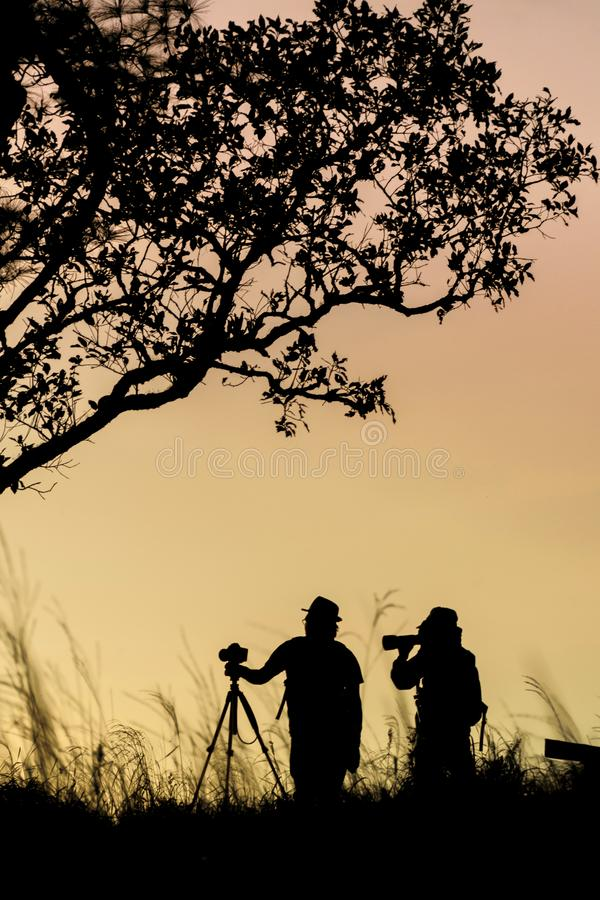 Silueta del fot?grafo que toma la imagen del paisaje durante salida del sol imagen de archivo