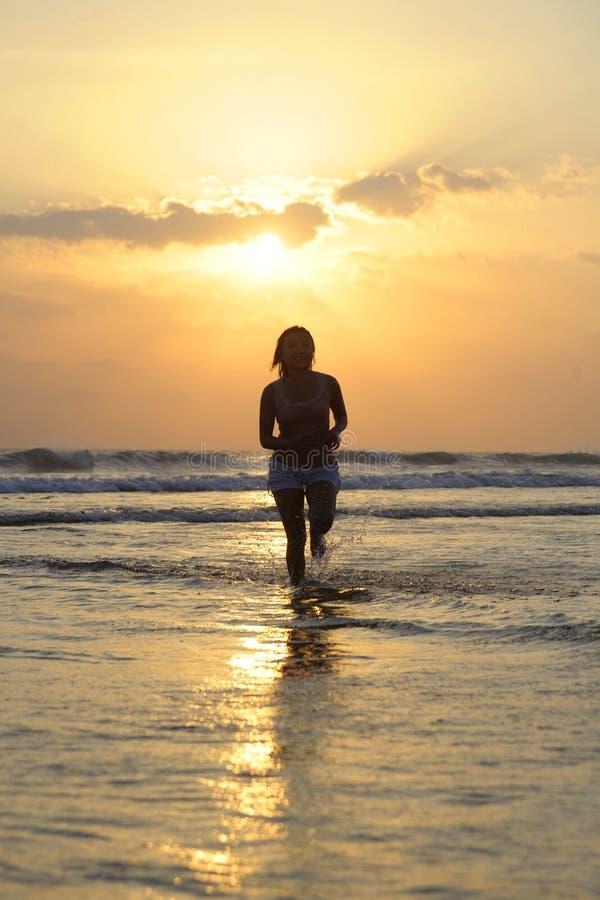 Silueta del funcionamiento asiático hermoso y atractivo joven de la mujer libre y feliz divirtiéndose en la playa de la puesta de imagenes de archivo