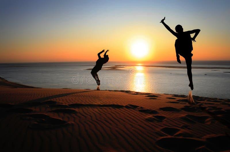 Silueta del gimnasta en la playa en la puesta del sol fotos de archivo libres de regalías