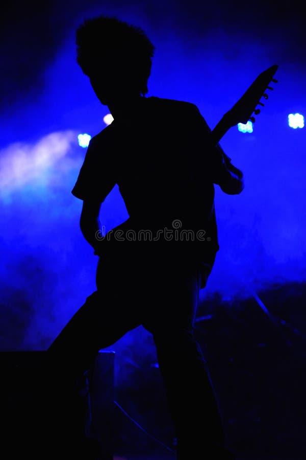 Silueta del guitarrista de la roca con el fondo azul en un concierto, la India foto de archivo libre de regalías