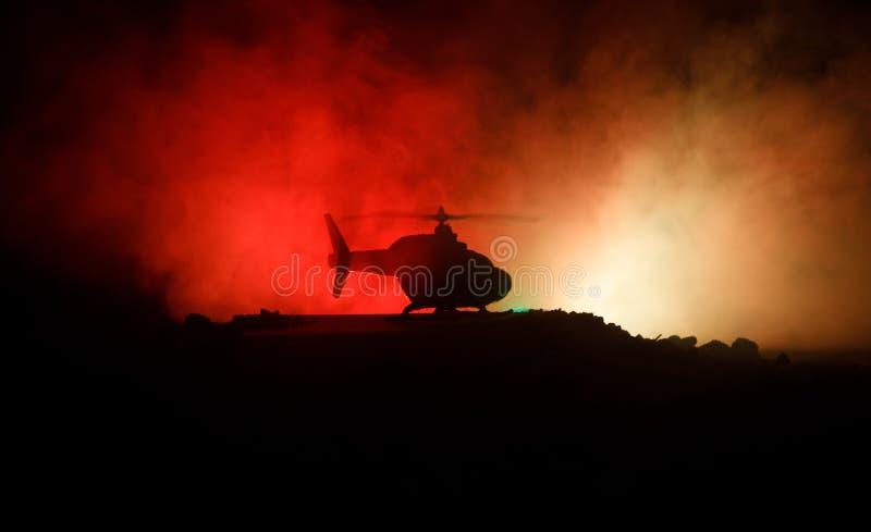 Silueta del helicóptero militar lista para volar de zona del conflicto Cantidad adornada de la noche con el helicóptero que comie fotografía de archivo libre de regalías