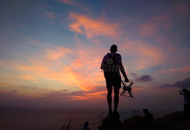 Silueta del helicóptero que controla y de fotografiar del viajero salida del sol colorida El hombre hace que la foto y el vídeo a imagen de archivo