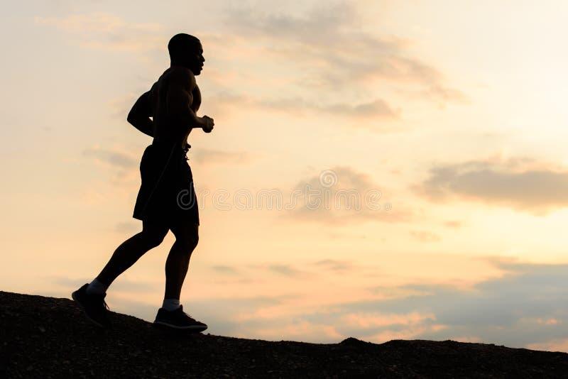 Silueta del hombre afroamericano del atleta que activa en puesta del sol en montañas Entrenamiento al aire libre Concepto del dep foto de archivo libre de regalías