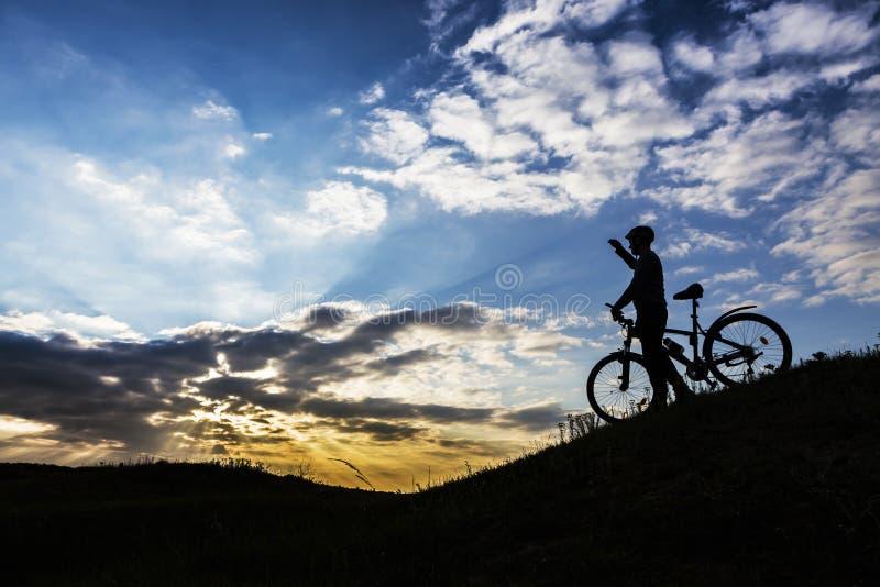 Silueta del hombre del ciclista y bici de monta?a fotos de archivo libres de regalías