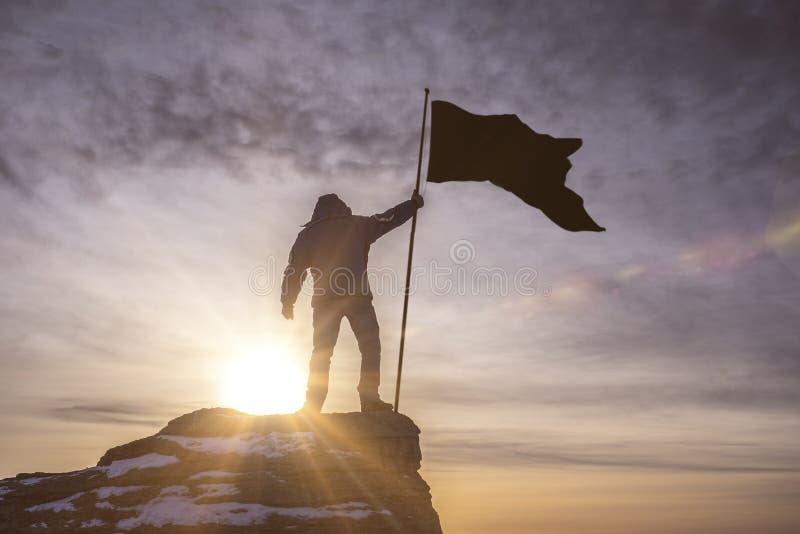 Silueta del hombre con la bandera de la victoria encima de una montaña sobre fondo ligero del cielo y del sol imagenes de archivo