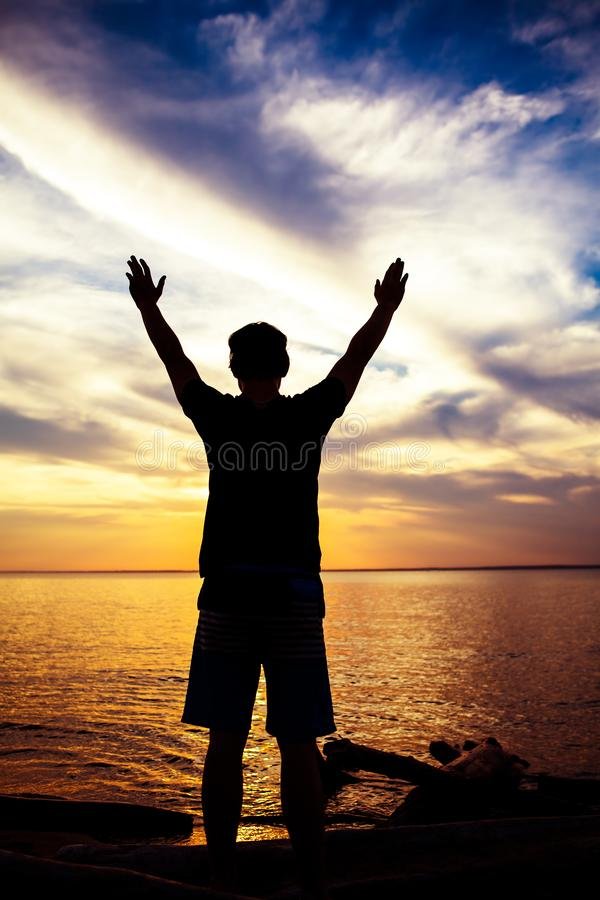Silueta del hombre con las manos para arriba fotografía de archivo libre de regalías