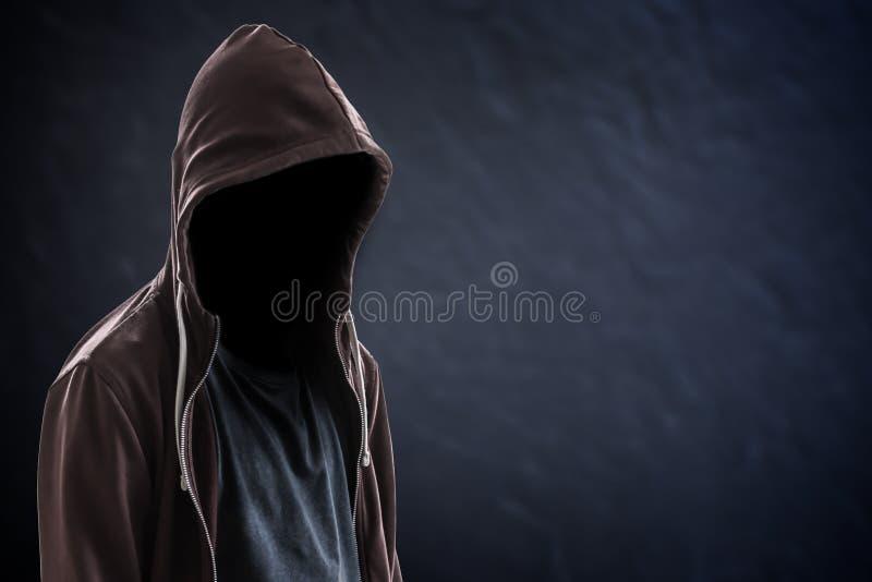 Silueta del hombre con una capilla, del fondo negro con el espacio de la copia, del criminal o del concepto del pirata informátic imagenes de archivo