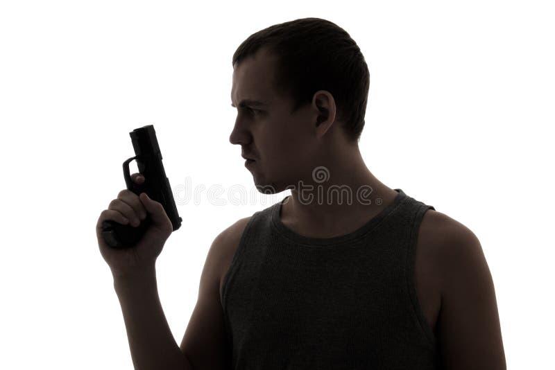 Silueta del hombre criminal que sostiene el arma aislado en blanco imágenes de archivo libres de regalías