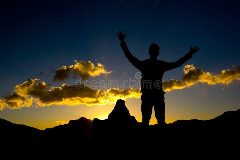 Silueta del hombre de negocios que se coloca en mountaint superior imagen de archivo libre de regalías