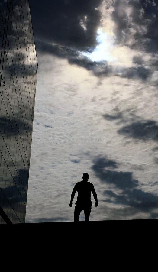 Silueta del hombre debajo del cielo nublado fotos de archivo libres de regalías
