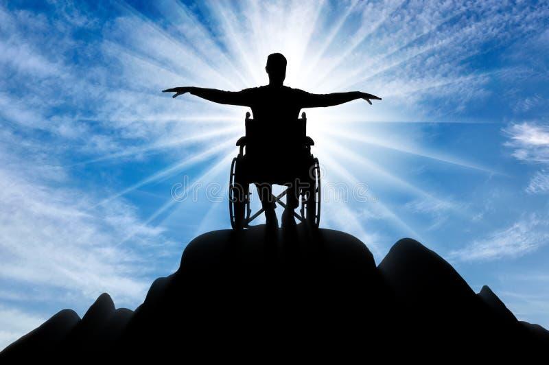 Silueta del hombre discapacitado feliz en silla de ruedas encima de la montaña fotos de archivo