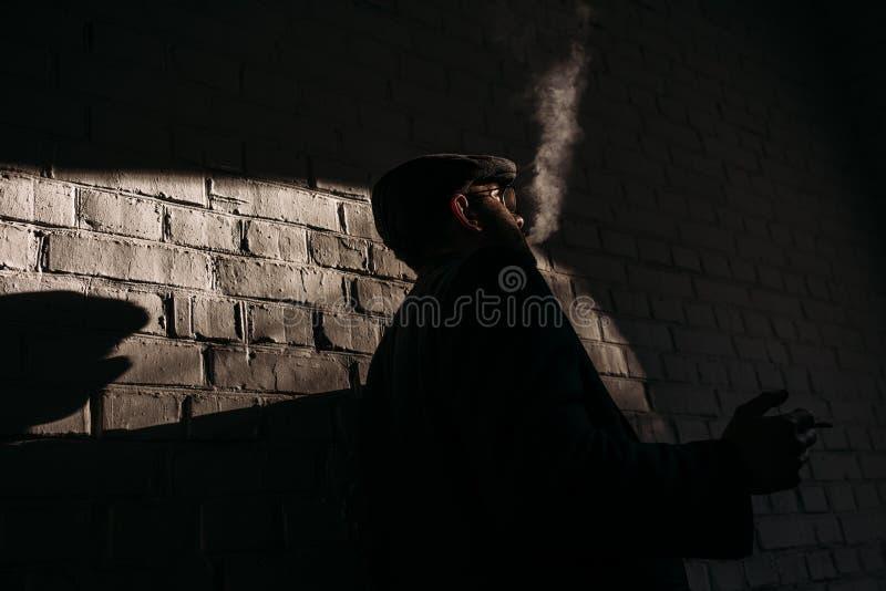 silueta del hombre elegante que fuma delante de fotos de archivo libres de regalías
