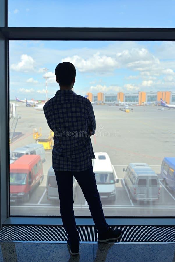 Silueta del hombre en aviones del vuelo del salón del aeropuerto que esperan para foto de archivo libre de regalías