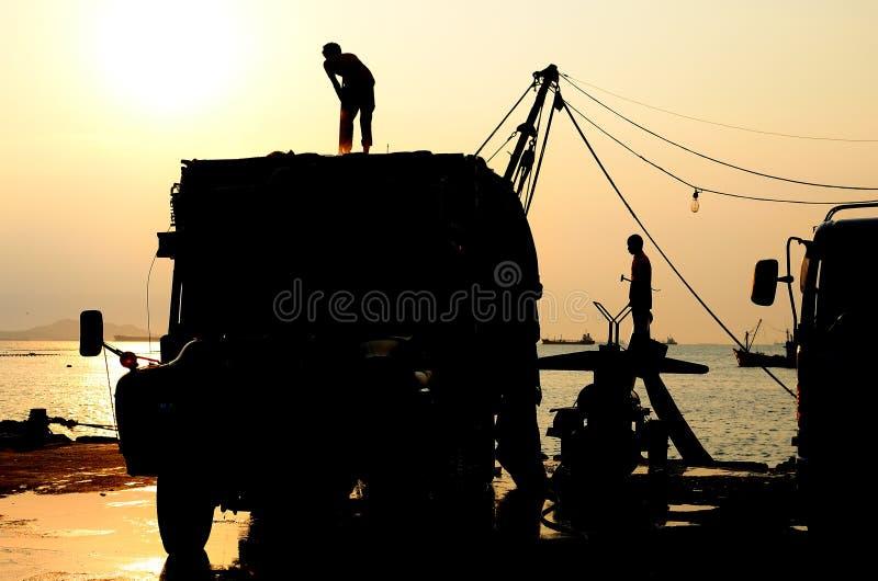 Silueta del hombre en el camión con el cielo de la puesta del sol foto de archivo