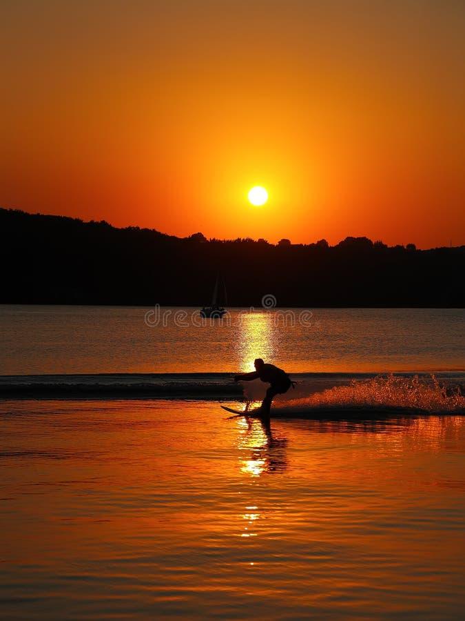 Silueta del hombre en los esquíes acuáticos en la puesta del sol imagen de archivo libre de regalías
