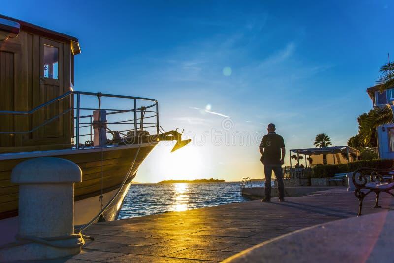 Silueta del hombre en rayos de la puesta del sol en el mar adriático en Tribunj en Croacia imagen de archivo libre de regalías